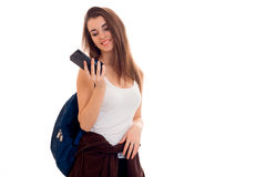Retrato de la muchacha atractiva joven del estudiante con la mochila azul y el teléfono móvil en las manos aisladas en el fondo b Fotografía de archivo libre de regalías