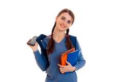 Retrato de la muchacha atractiva joven del estudiante con la mochila y los cuadernos aislados en el fondo blanco Imagen de archivo