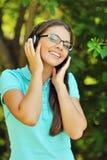 Retrato de la muchacha atractiva joven que escucha la música con el headph Imagen de archivo