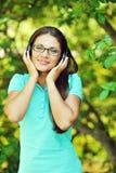 Retrato de la muchacha atractiva joven que escucha la música con el headph Imagenes de archivo