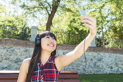 Retrato de la muchacha atractiva joven que escucha la música con el headph Fotografía de archivo