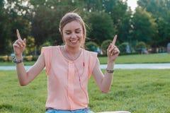 Retrato de la muchacha atractiva joven que escucha la música con los auriculares Imagen de archivo libre de regalías