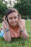 Retrato de la muchacha atractiva joven que escucha la música con los auriculares Imagen de archivo