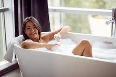 Retrato de la muchacha atractiva que miente en bañera fotos de archivo