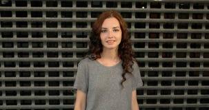 Retrato de la muchacha atractiva que presenta cerca de la pared de la seguridad o de la cerca metálica del área restricta metrajes