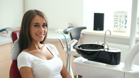 Retrato de la muchacha atractiva que se sienta en silla dental y que sonríe en la cámara lentamente almacen de metraje de vídeo