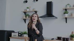Retrato de la muchacha auténtica extraordinaria expresiva que baile y canto en la cocina Ella atractivo negro que lleva almacen de metraje de vídeo