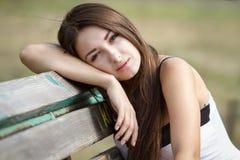 Retrato de la muchacha bastante adolescente en un banco Foto de archivo
