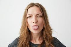 Retrato de la muchacha bastante divertida de los jóvenes que mira la cámara que muestra la lengua sobre el fondo blanco Foto de archivo