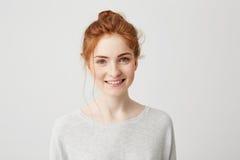 Retrato de la muchacha blanda feliz del jengibre con los ojos azules y las pecas que miran la cámara que sonríe sobre el fondo bl Fotos de archivo libres de regalías