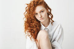 Retrato de la muchacha blanda linda del jengibre con el pelo rizado que mira la cámara sobre el fondo blanco Foto de archivo