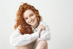 Retrato de la muchacha blanda linda del jengibre con el pelo rizado que sonríe sobre el fondo blanco Imagen de archivo libre de regalías