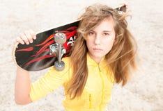 Retrato de la muchacha bonita con el monopatín al aire libre. Foto de archivo libre de regalías