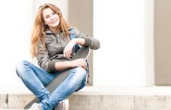 Retrato de la muchacha bonita con el monopatín al aire libre. Fotos de archivo libres de regalías