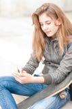 Retrato de la muchacha bonita con el monopatín al aire libre. Imágenes de archivo libres de regalías