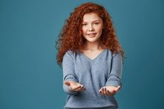Retrato de la muchacha bonita con el pelo y las pecas rojos ondulados en la camisa gris que tira de las manos in camera con feliz Imagen de archivo
