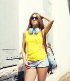 Retrato de la muchacha bonita con los auriculares y la mochila Imagen de archivo libre de regalías
