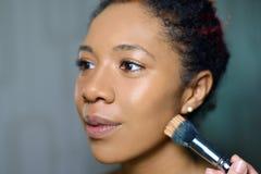 Retrato de la muchacha bonita con maquillaje hermoso el amo hace rostro con el cepillo foto de archivo
