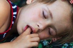 Retrato de la muchacha bonita durmiente del niño que chupa su finger mientras que duerme fotografía de archivo libre de regalías