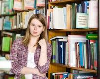 Retrato de la muchacha bonita en la biblioteca que mira la cámara Fotografía de archivo