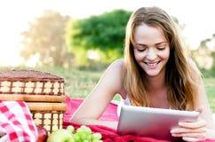 Retrato de la muchacha bonita en parque con su tableta Imágenes de archivo libres de regalías