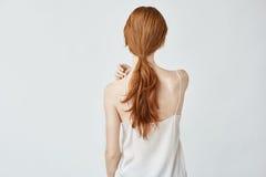 Retrato de la muchacha bonita joven con el pelo astuto que presenta de nuevo a cámara Fotos de archivo