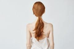 Retrato de la muchacha bonita joven con el pelo astuto que presenta de nuevo a cámara Imagen de archivo libre de regalías