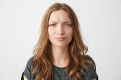 Retrato de la muchacha bonita joven descontentada que mira la cámara con desprecio sobre el fondo blanco Foto de archivo libre de regalías