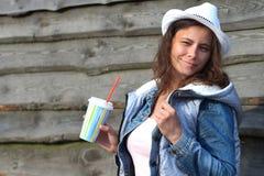 Retrato de la muchacha bonita joven en sombrero de vaquero con batido de leche a disposición Mujer atractiva en chaqueta de los v imagen de archivo libre de regalías