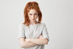 Retrato de la muchacha bonita joven resentida del pelirrojo que mira la cámara brutal con los brazos cruzados sobre el fondo blan Imagen de archivo libre de regalías