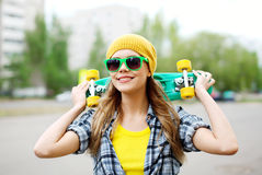 Retrato de la muchacha bonita sonriente en gafas de sol con el monopatín Imagen de archivo