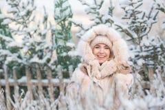 Retrato de la muchacha bonita sonriente en una chaqueta beige en un fondo de las piceas en un invierno fotos de archivo