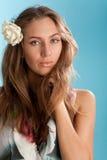 Retrato de la muchacha brown-haired atractiva sobre azul imagen de archivo libre de regalías