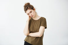 Retrato de la muchacha cansada aburrida descontentada con el bollo sobre el fondo blanco Imágenes de archivo libres de regalías