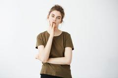 Retrato de la muchacha cansada aburrida descontentada con el bollo sobre el fondo blanco Fotografía de archivo libre de regalías