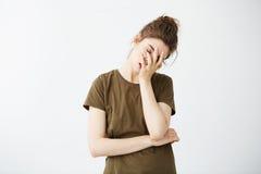 Retrato de la muchacha cansada aburrida descontentada con el bollo sobre el fondo blanco Foto de archivo libre de regalías