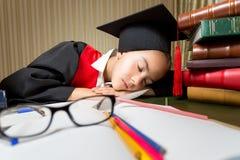 Retrato de la muchacha cansada en el casquillo de la graduación que filtra en la biblioteca Imágenes de archivo libres de regalías