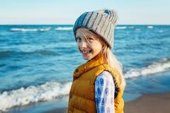 Retrato de la muchacha caucásica blanca rubia sonriente del niño del niño con el pelo largo, el gilet de la chaqueta amarilla que Foto de archivo libre de regalías