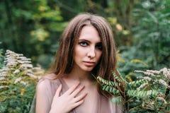 Retrato de la muchacha caucásica hermosa en hojas verdes Foco suave imagen de archivo