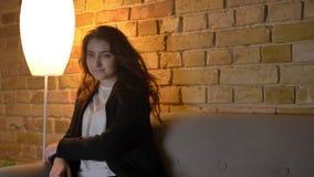 Retrato de la muchacha caucásica joven con el pelo ondulado que elige el canal en la TV y que mira con interés en hogar acogedor almacen de video