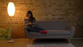 Retrato de la muchacha caucásica joven que se sienta en el sofá y que mira en el smartphone risueñamente en fondo casero acogedor almacen de video