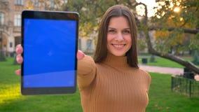 Retrato de la muchacha caucásica joven que usa la tableta y mostrando su exhibición a la cámara en fondo verde del parque almacen de metraje de vídeo