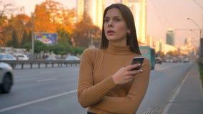 Retrato de la muchacha caucásica morena cansada que se coloca nervioso cerca del camino con el teléfono en manos almacen de metraje de vídeo