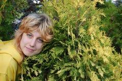 Retrato de la muchacha cerca del arbusto. Foto de archivo