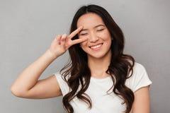 Retrato de la muchacha china graciosamente 20s en la camiseta casual que tiene fu Foto de archivo libre de regalías