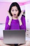 Retrato de la muchacha chocada con el ordenador portátil Foto de archivo