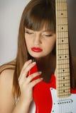 Retrato de la muchacha con la guitarra roja Foto de archivo
