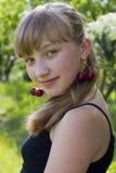 Retrato de la muchacha con las cerezas en los oídos Foto de archivo