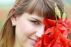 Retrato de la muchacha con las flores de la amapola Foto de archivo libre de regalías