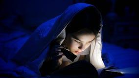 Retrato de la muchacha con la linterna que lee el libro asustadizo en la noche Fotografía de archivo libre de regalías